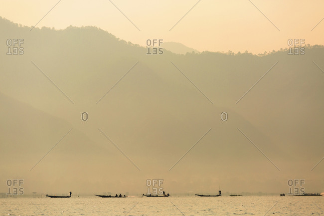Silhouette of canoes floating on rural lake