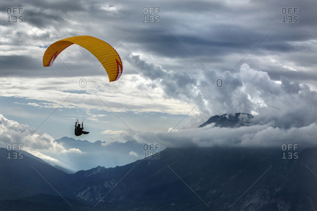Caucasian man paragliding over remote mountains