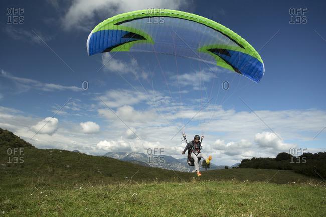 Caucasian man paragliding into remote field