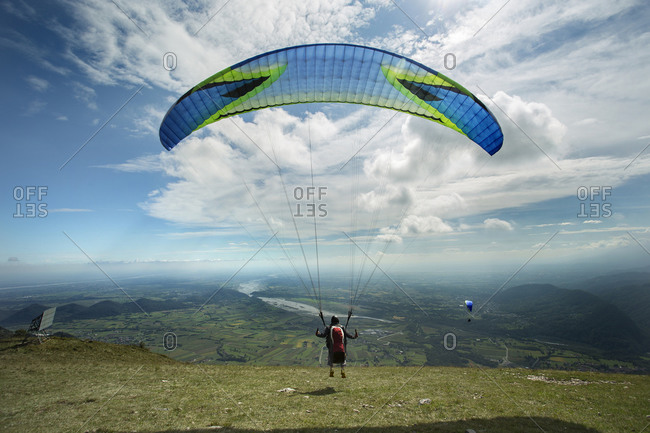 Caucasian man paragliding into remote field