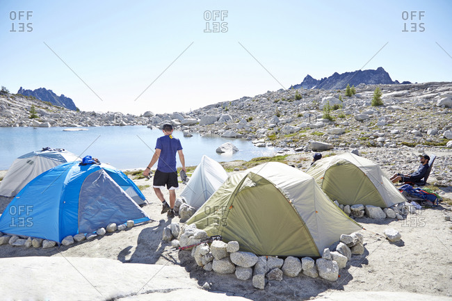 Man walking by tents at campsite in desert landscape