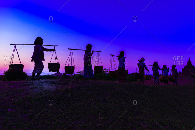 Silhouette of people carrying baskets under sunset sky