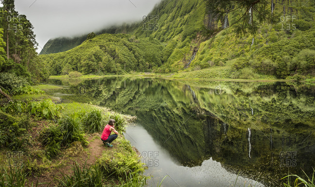 Hiker crouching at still lake in remote mountains