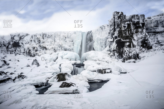 Waterfall pouring over icy cliffs in remote landscape