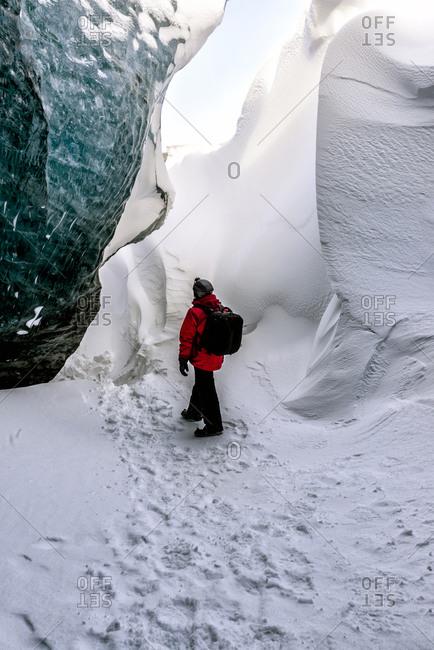 Hiker walking in snowy ice cave
