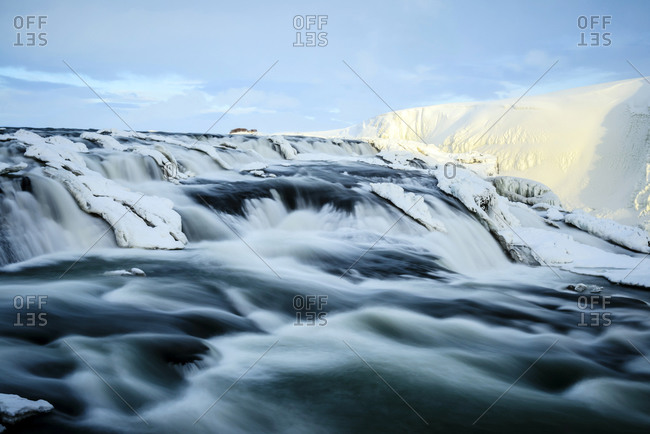 Time lapse view of river flowing over icy rock formations