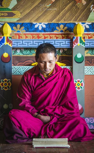 Asian monk reading on temple floor