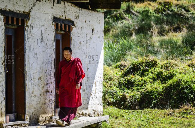 Asian monk walking by monastery doors