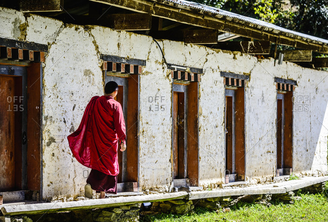 Asian monk walking by monastery doors