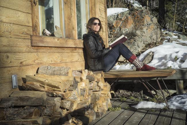 Caucasian woman reading book on cabin porch
