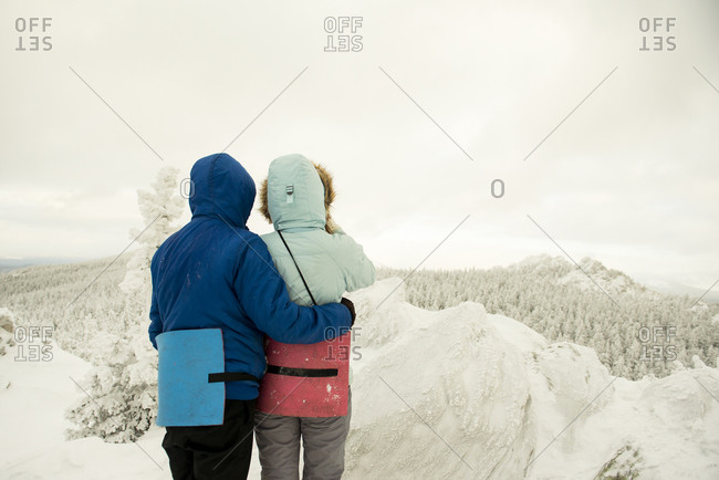 Caucasian hikers on mountaintop admiring snowy landscape