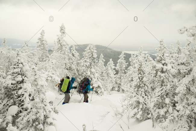 Caucasian hikers walking in snowy forest