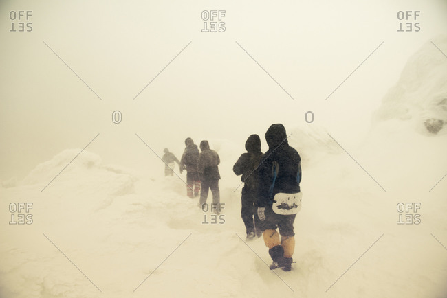 Caucasian hikers walking on snowy path