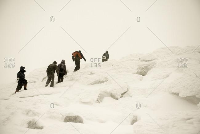 Caucasian hikers climbing snowy mountain