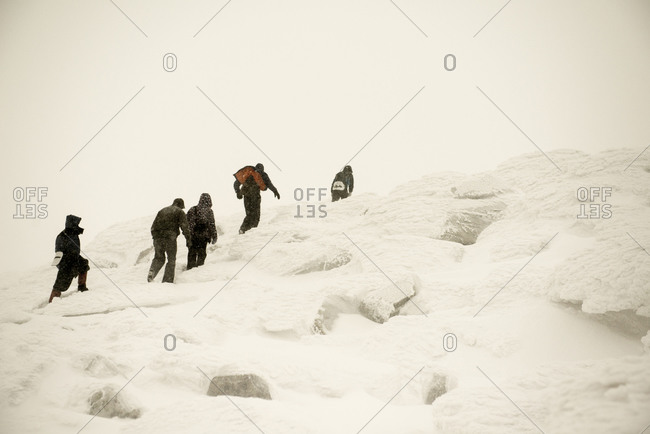 Caucasian hikers climbing snowy mountain