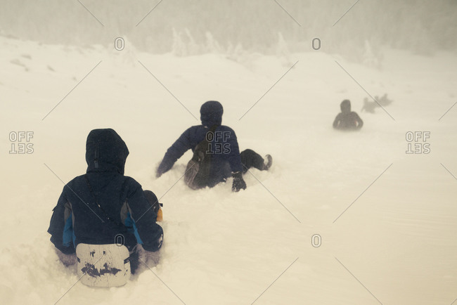 Caucasian hikers sledding on snowy hill