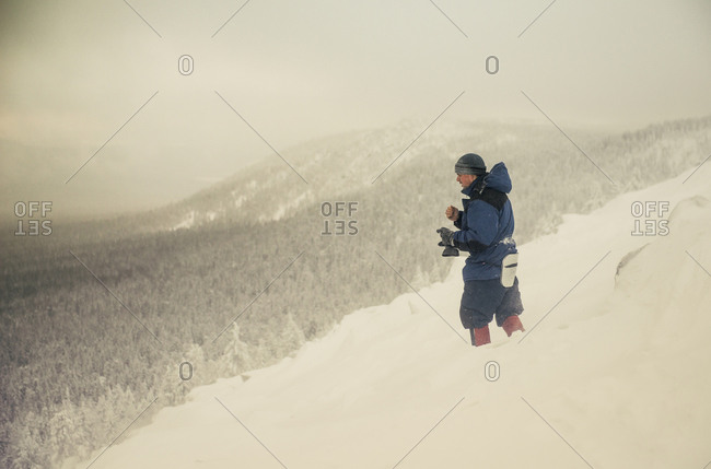 Caucasian hiker standing on snowy mountain