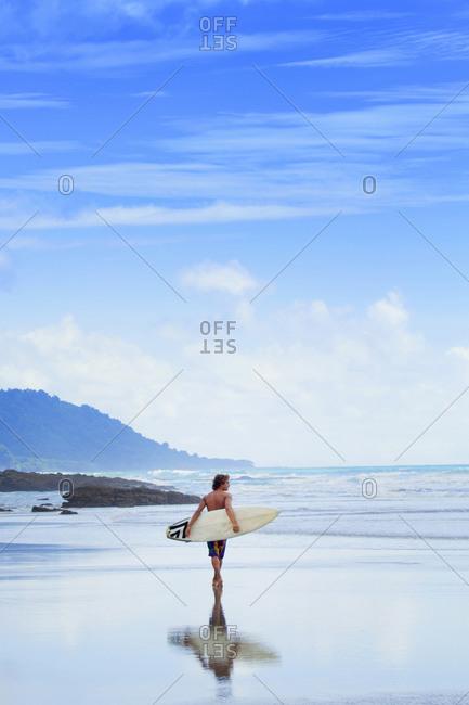 Man carrying surfboard on beach