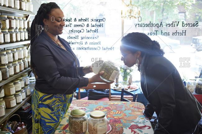 Black woman smelling tea in tea shop