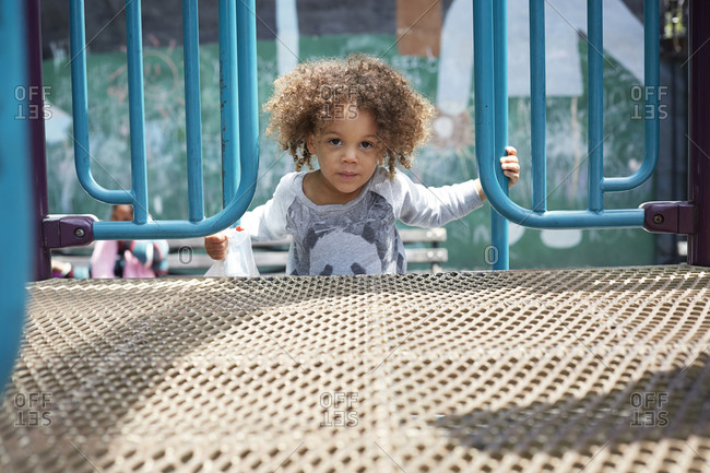 Mixed race boy climbing on play structure