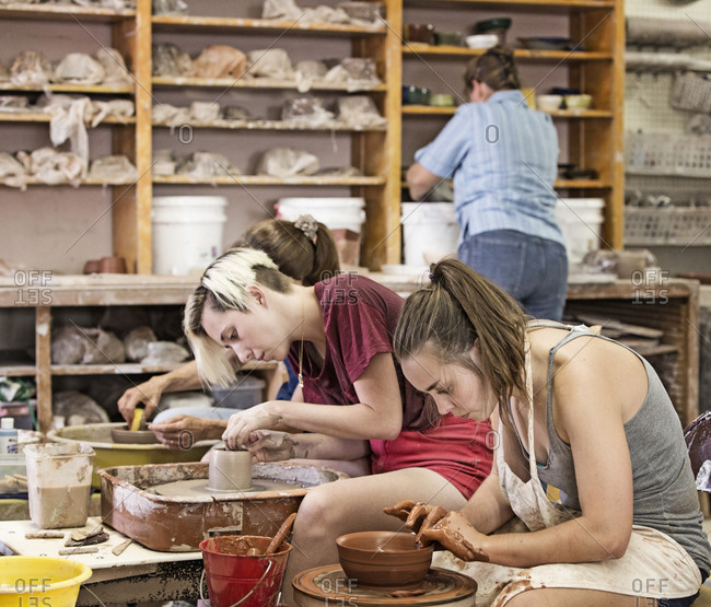 Students working on pottery wheels in studio