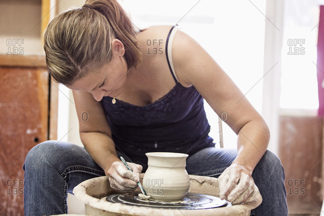 Caucasian student working on pottery wheel in studio