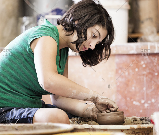 Student shaping pottery on wheel in ceramic studio