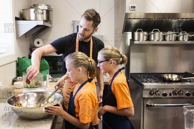 Teacher and students tossing salad in cooking class