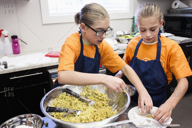 Caucasian girls tossing salad in cooking class