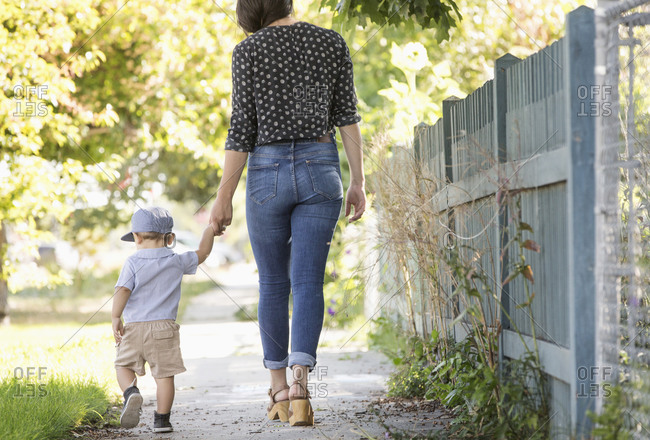 Mixed race mother and son walking in neighborhood