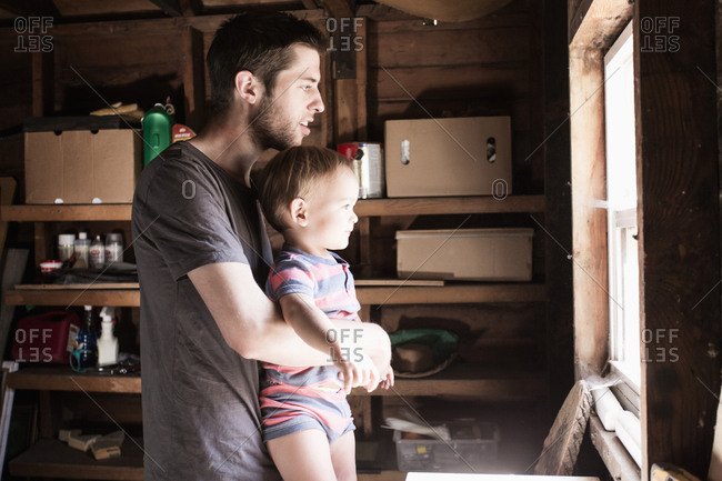 Father and son looking out window