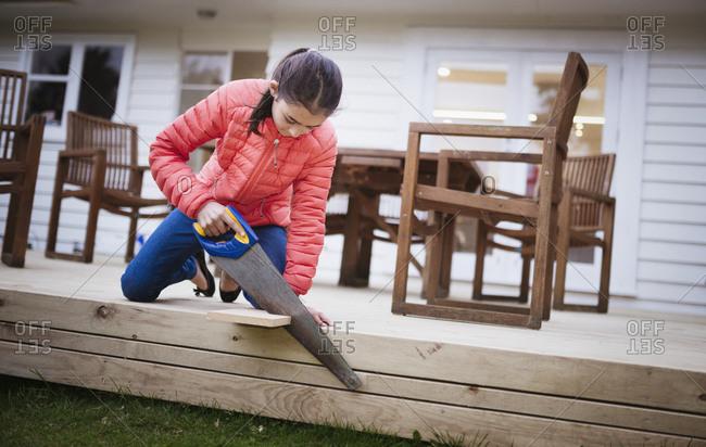 Mixed race girl sawing wood in backyard