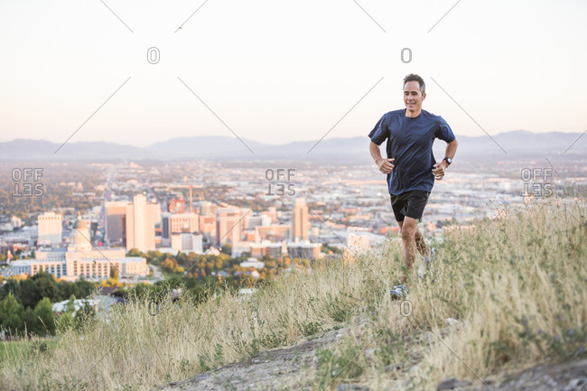 Mixed race man running on hilltop over Salt Lake City, Utah, United States