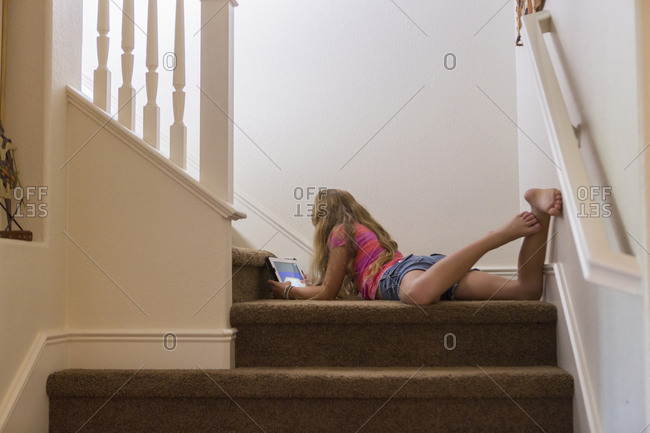 Caucasian girl using digital tablet on stairs