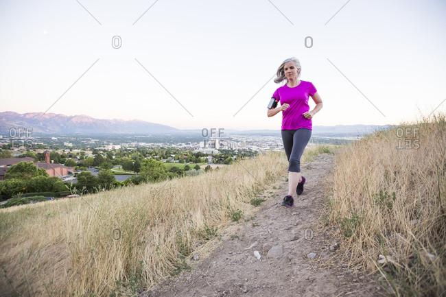 Caucasian woman running on hilltop