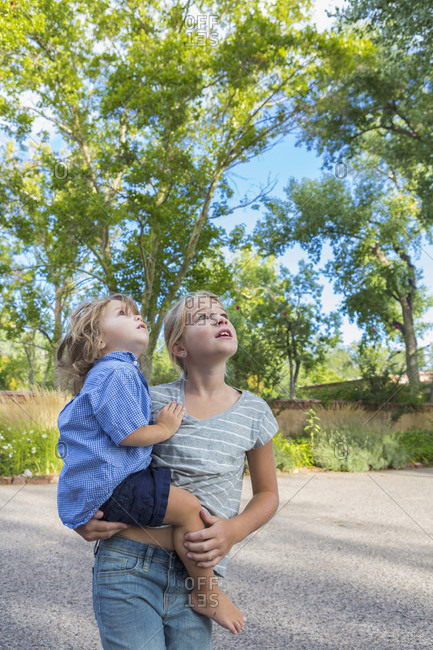 Caucasian girl holding toddler brother outdoors