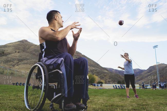 Paraplegic athlete in wheelchair with girlfriend tossing ball