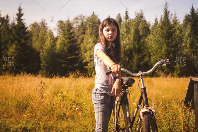 Caucasian teenage girl pushing bicycle in field