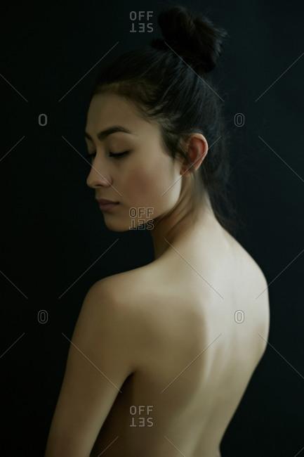 Nude Hispanic woman looking down