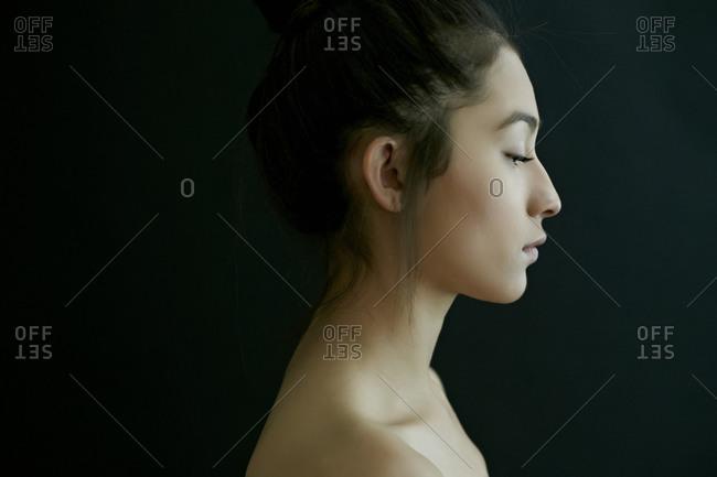 Profile of nude Hispanic woman looking down