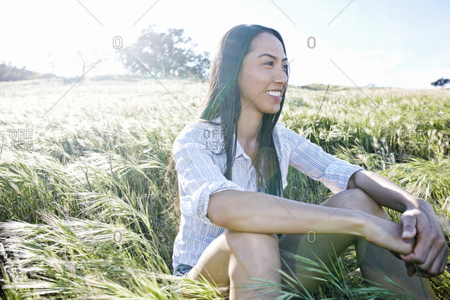 Mixed race woman sitting in field