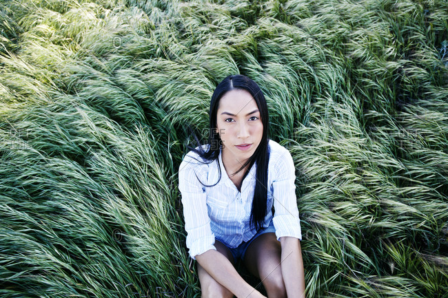 Mixed race woman sitting in grass