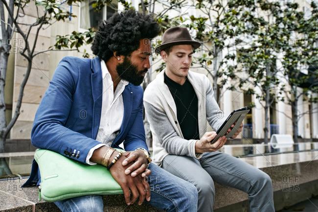 Businessmen using digital tablet outdoors