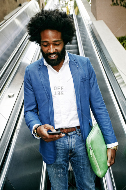 Mixed race businessman using cell phone on escalator