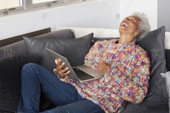 African American woman using laptop on sofa
