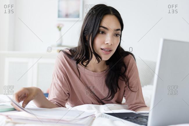 Hispanic woman paying bills on laptop
