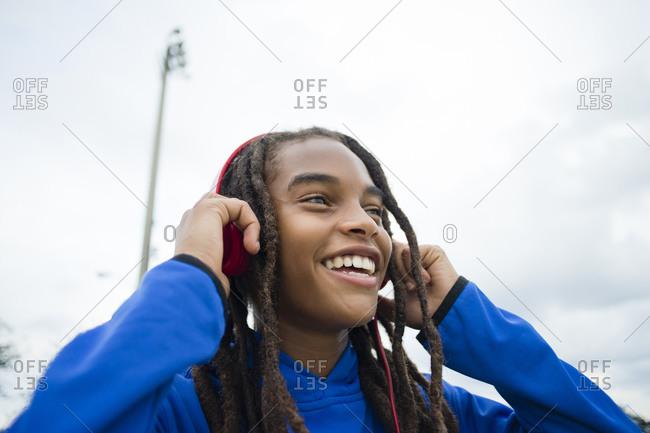 Mixed race boy listening to headphones outdoors