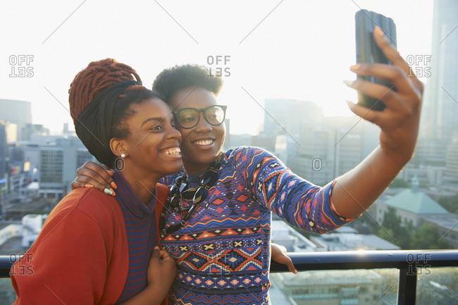 Women taking selfie on city rooftop