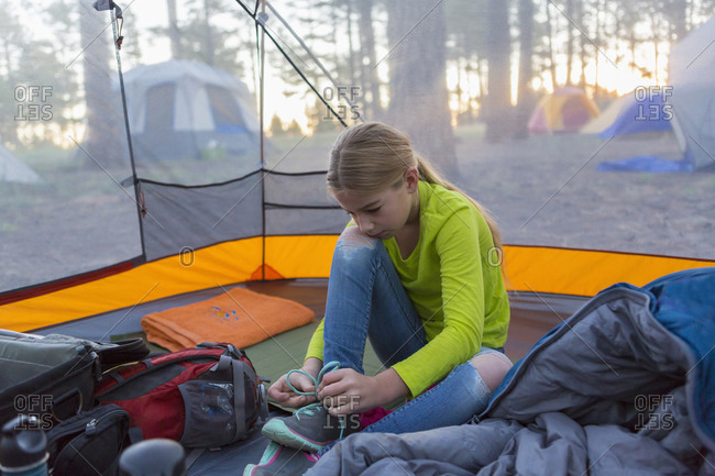 Caucasian girl tying shoes in camping tent