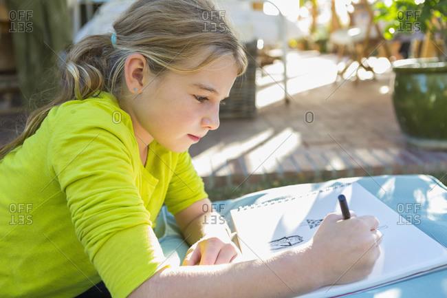 Caucasian girl drawing outdoors